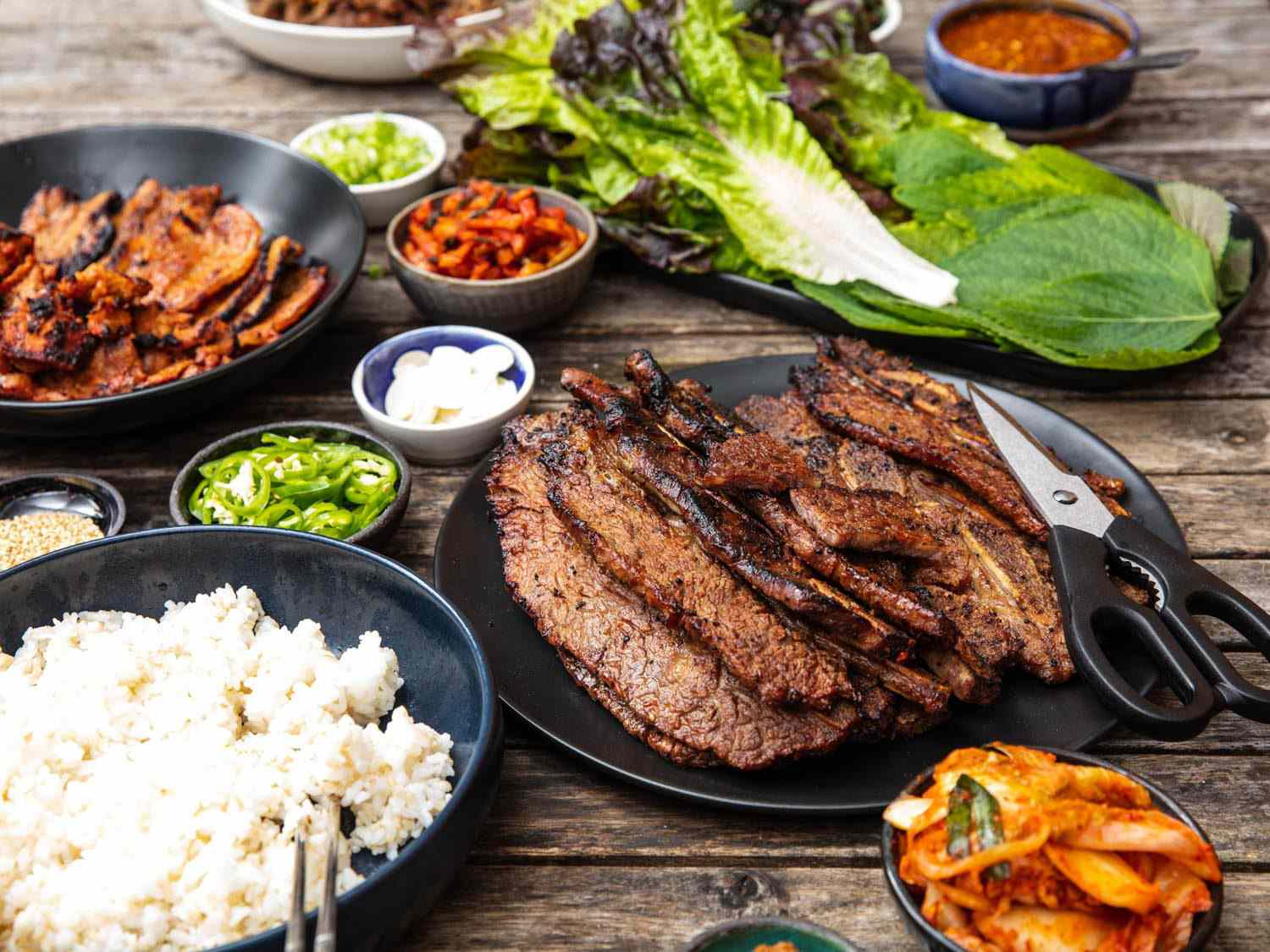 Side view of a table set with a Korean barbecue spread, with a plate of beef galbi in the foreground.