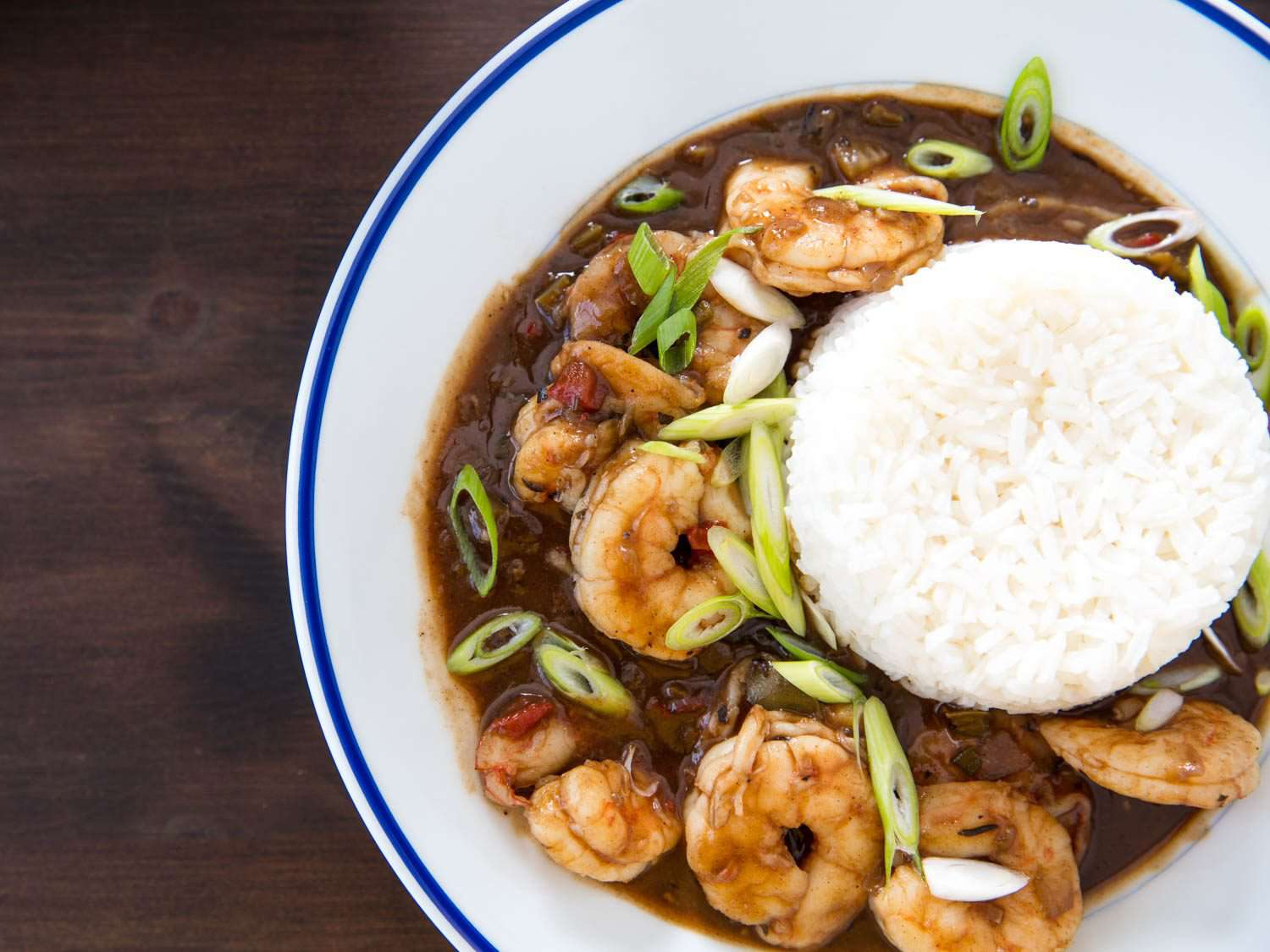 Beauty shot of shrimp etouffee, made with a dark brown roux, on the plate with rice