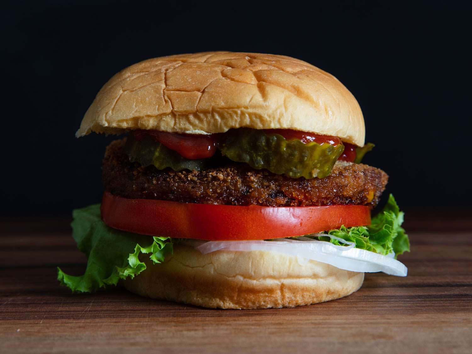 Side view of Trader Joe's Quinoa Cowboy black bean burger in a bun with tomato, onion, pickles, and lettuce
