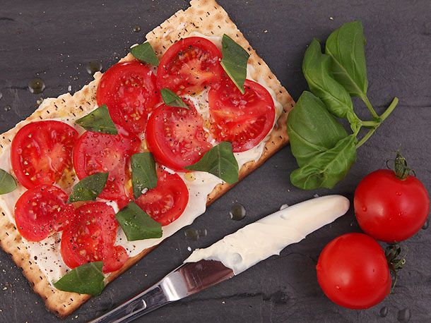 A piece of matzo layered with mayonnaise, tomato slices, and basil leaves, next to a butter knife, whole tomatoes, and more basil leaves