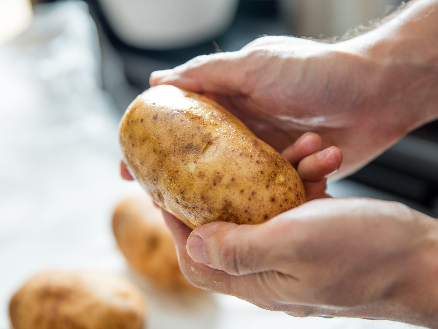 Two hands washing potato in sink.