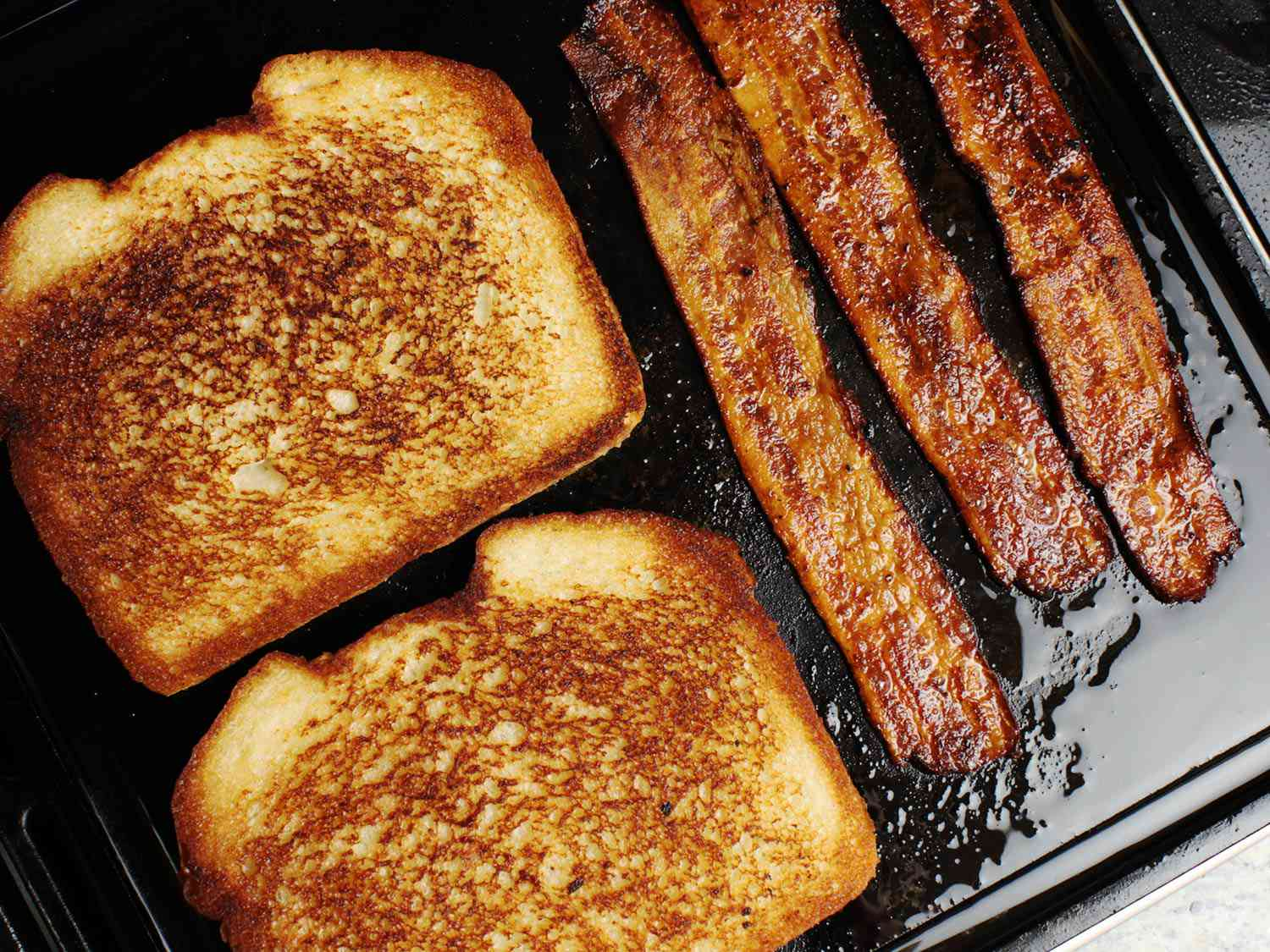 Two slices of sandwich bread toasting next to three strips of bacon on a griddle