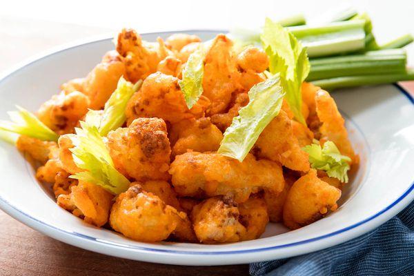 A plate of crispy buffalo fried cauliflower, with celery sticks on the side of the plate.