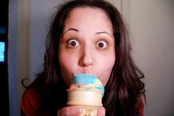 A woman eating Superman ice cream on a cone.