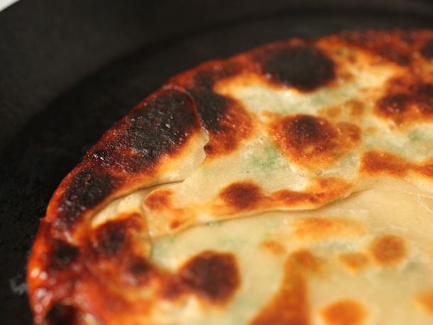 Close up photo of a scallion pancake with an overcooked edge.