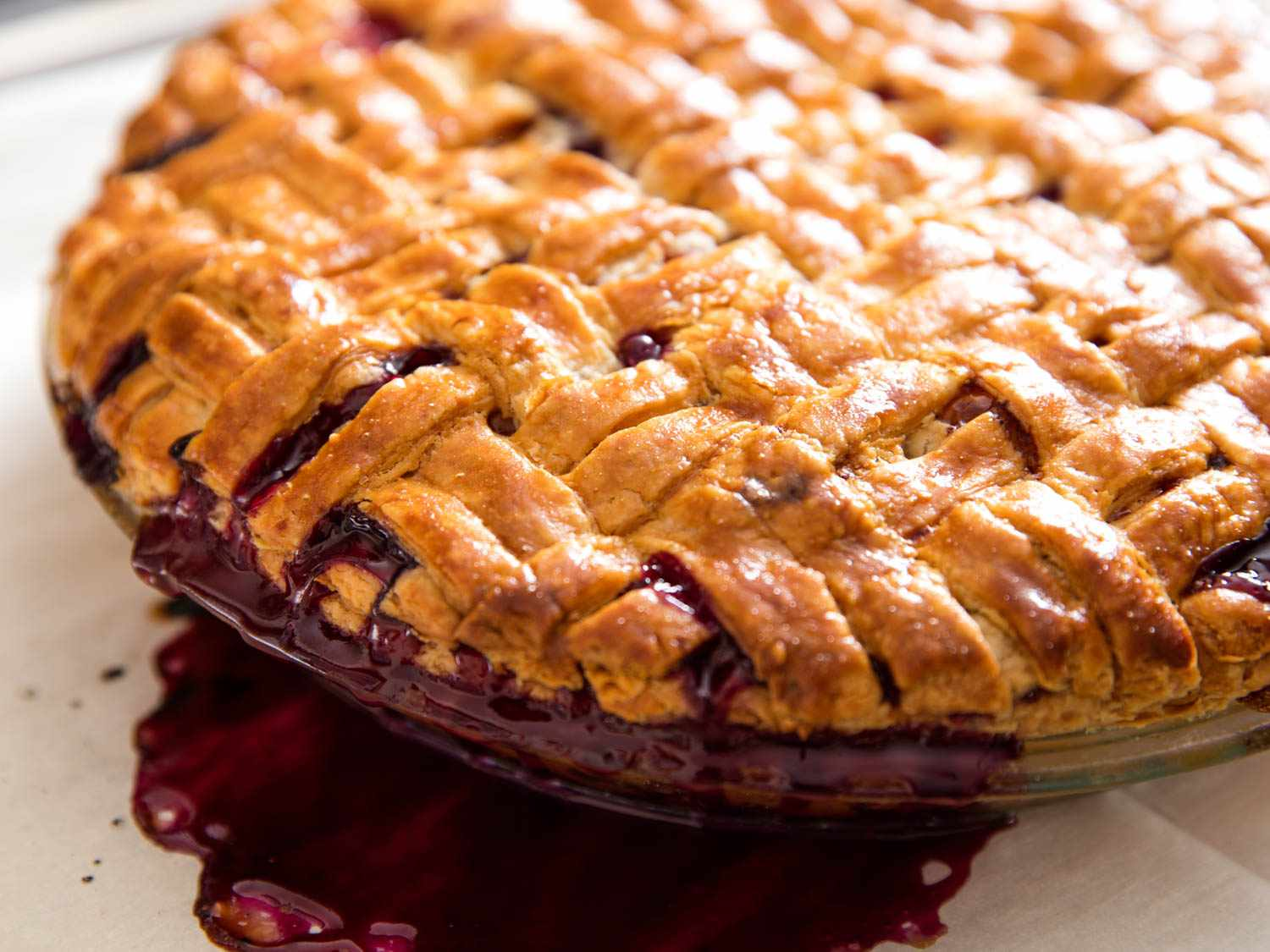 A lattice-topped mixed-fruit pie in a glass pie dish, with filling bubbling over onto parchment paper