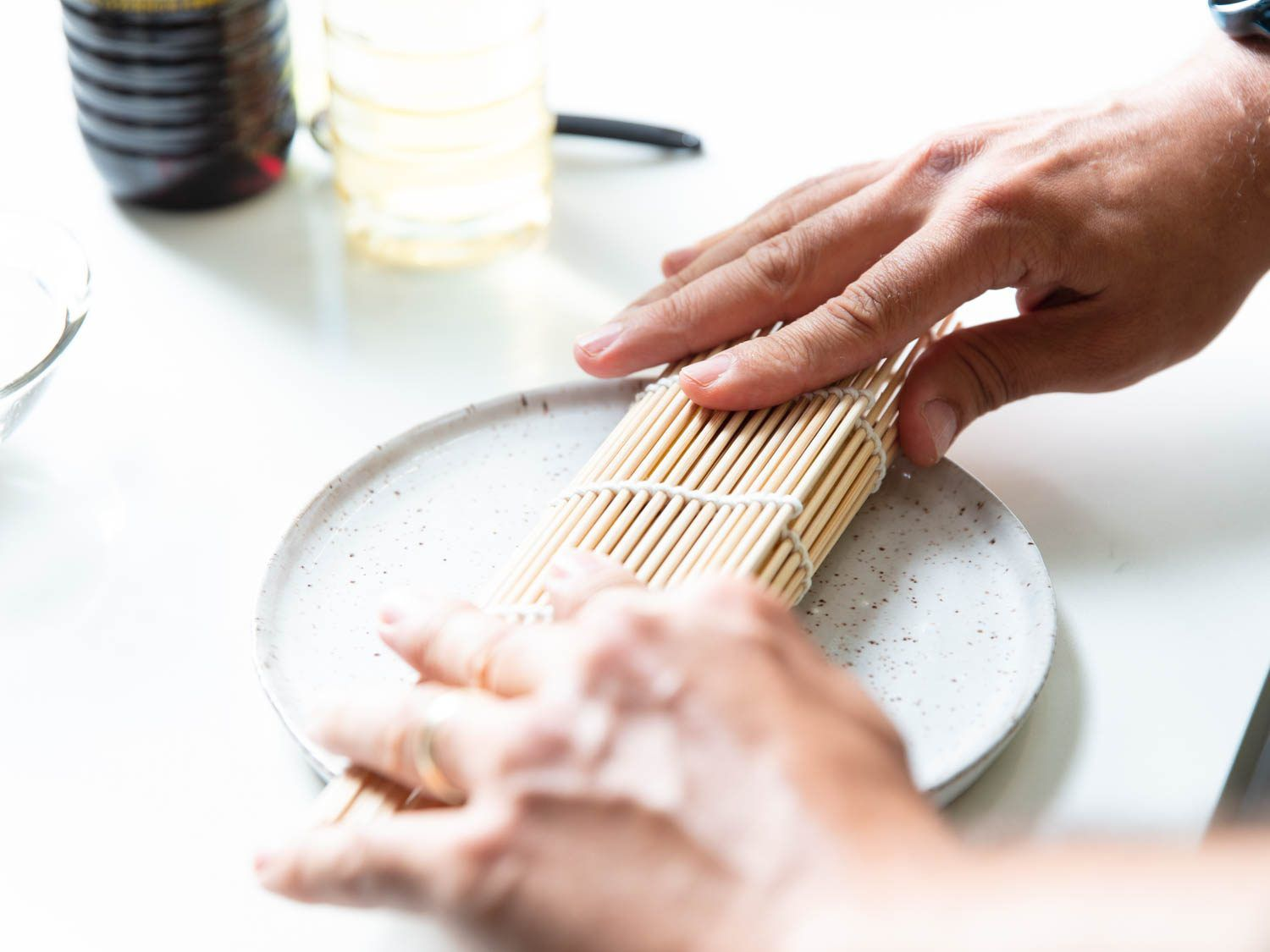 After cooking, tamagoyaki can be rolled up in a bamboo sushi mat to help set its rectangular shape; this photo shows the mat being rolled around the tamagoyaki.