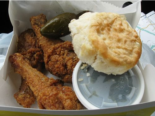 Fried chicken and a biscuit in a paper takeout box.