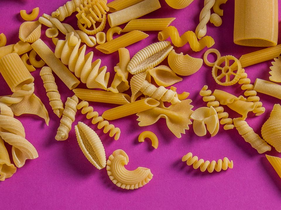 Overhead of mixed dried pasta shapes.