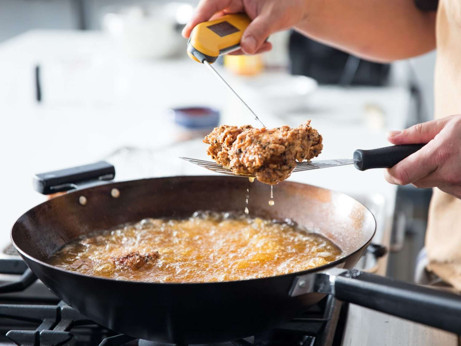 Digital thermometer being used to test the doneness of a piece of fried chicken, held aloft over a wok filled with bubbling oil and more pieces of frying chicken.