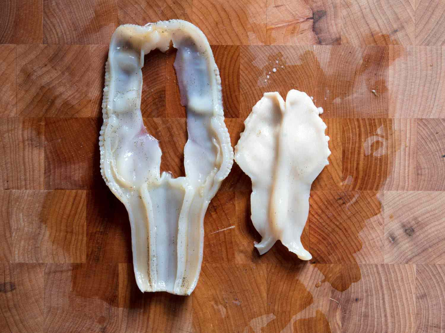 Cleaned razor clam meat on a wooden cutting board