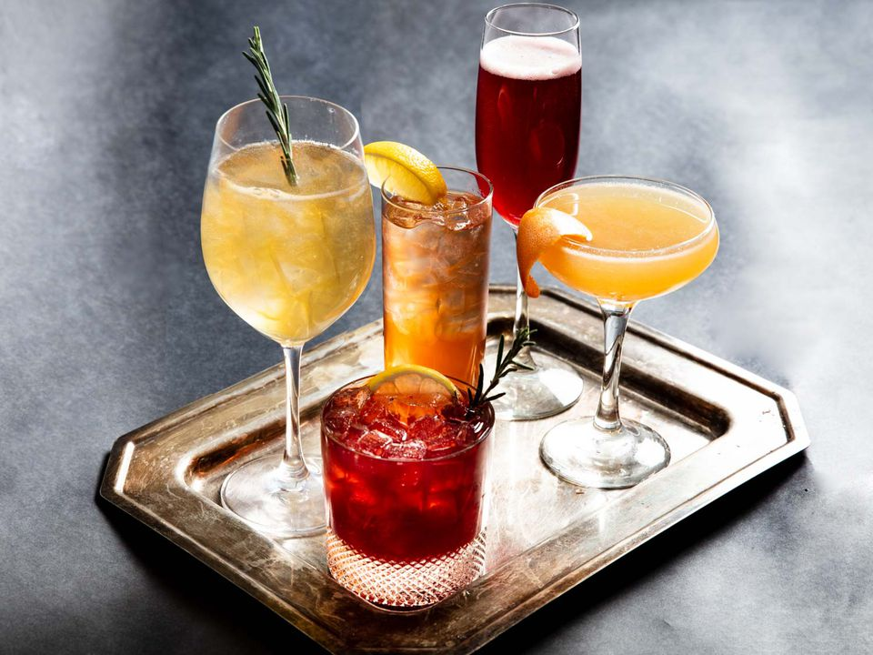 A tray with five glasses holding five different holiday cocktails
