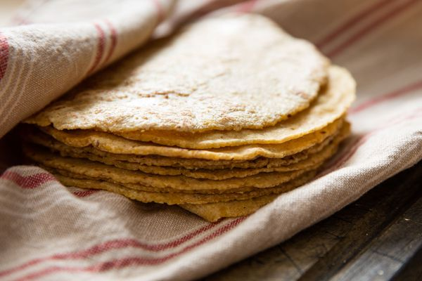 A stack of corn tortillas in a kitchen towel.