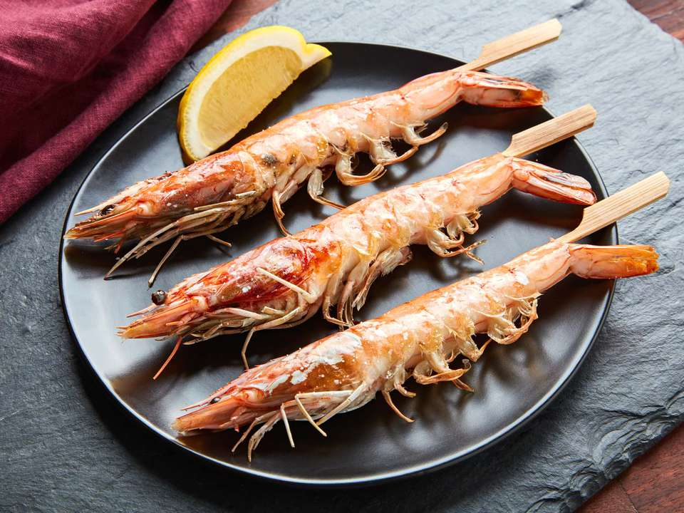 Three cooked head-on shrimp on skewers on a black plate with a lemon wedge.