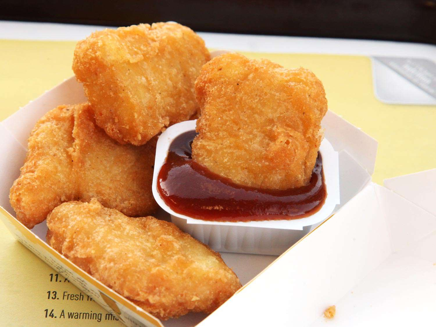 A box of chicken McNuggets from McDonald's with one nugget dipped in a container of sauce