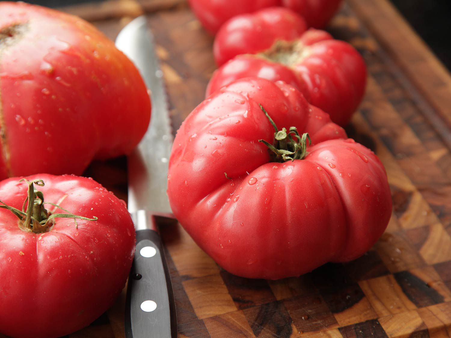 Red ripe tomatoes on a wooden cutting board, next to a knife