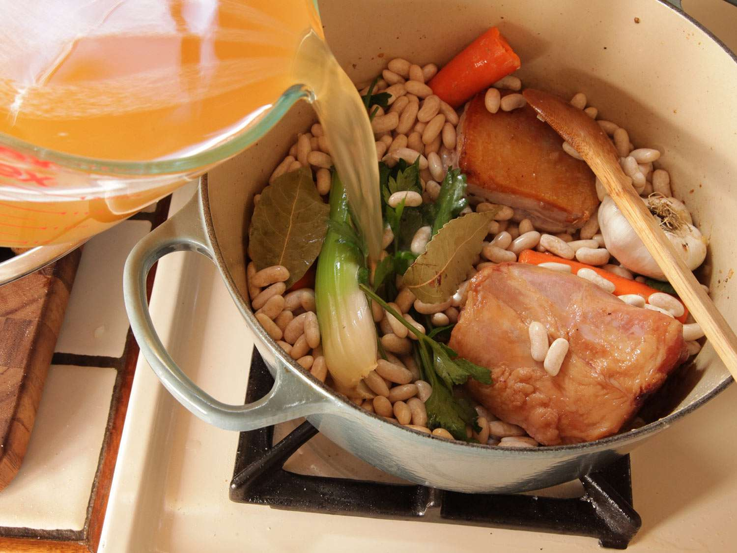 Adding stock to pot of dried beans, pork belly, ham hock, and aromatics for cassoulet.