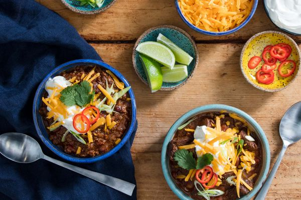 Two bowls of pressure cooker chili topped with cheese, sour cream, cilantro, chile slices, and lime wedges.
