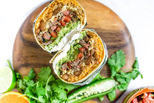 A Carne Asada burrito cut in half, exposing the rice, beans, steak, salsa and other fillings.