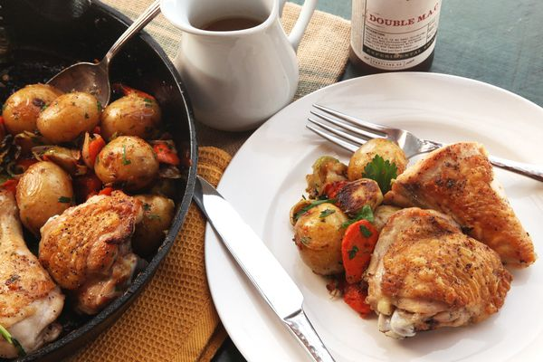 A plate of crisp-skinned chicken with roasted vegetables next to a skillet of chicken and vegetables.