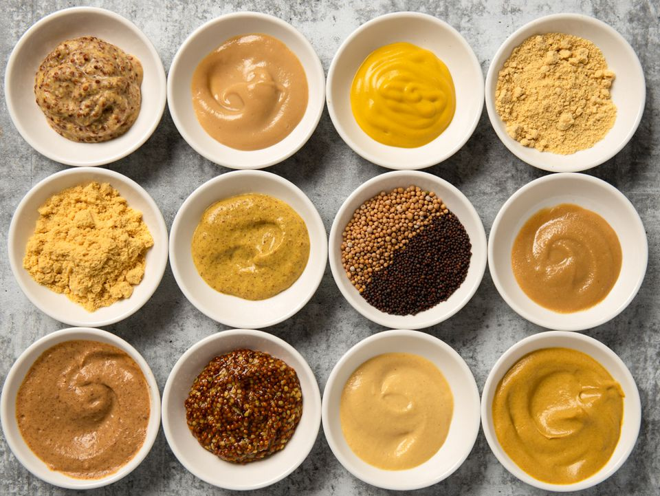a variety of mustard styles/products in small white bowls in a 4x3 grid