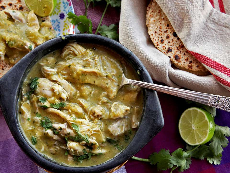Bowl of pressure cooker green chili chicken (chile verde) with tortillas, cilantro, and limes