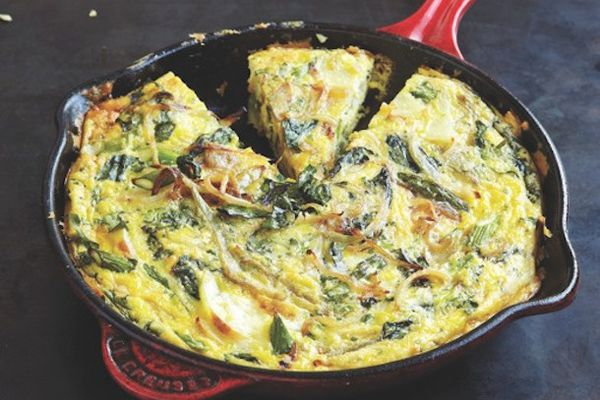 A frittata in a skillet with a wedge cut out.