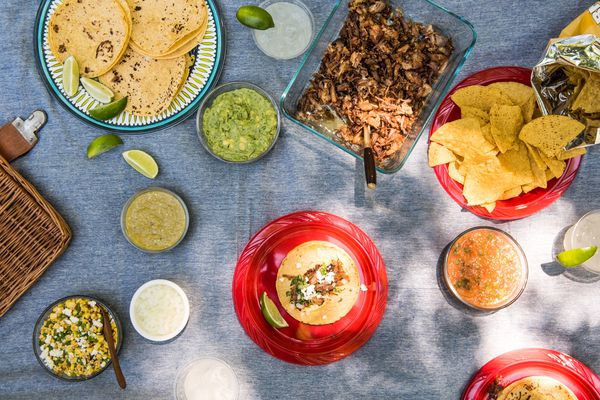 Snacks, dips, tortillas, lime wedges, salads, and dips as part of a Mexican-themed picnic spread on a picnic blanket.