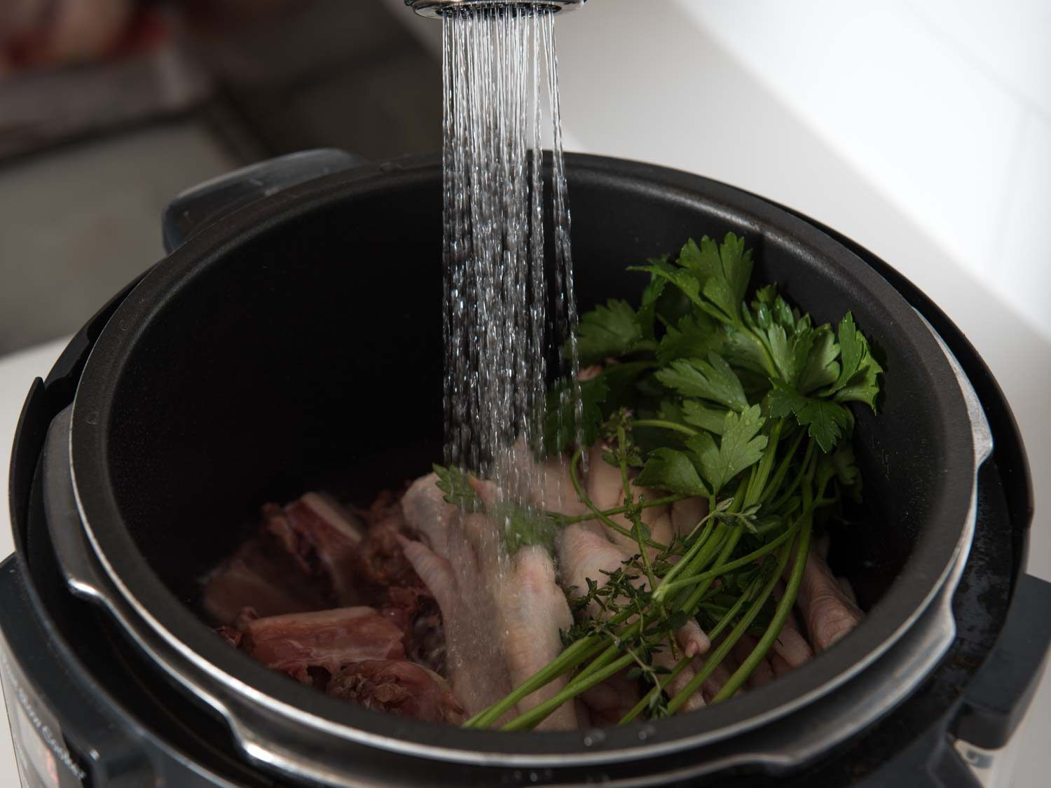Filling a multi-cooker with water and ingredients for chicken stock