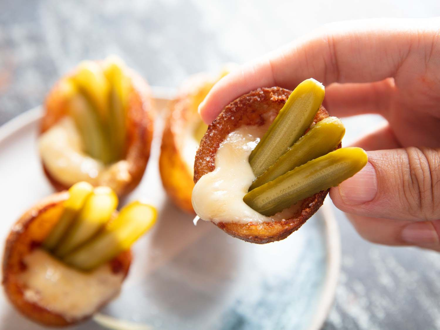 Deep-fried potato skin cups filled with melted raclette cheese ad thinly sliced gherkins.