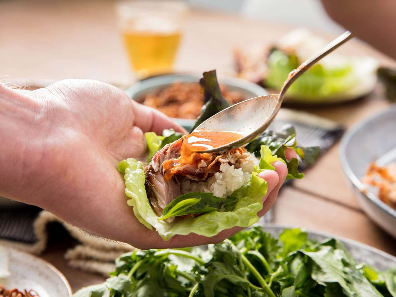 Spooning dipping sauce over a lettuce wrap with pork, sticky rice, and herbs.