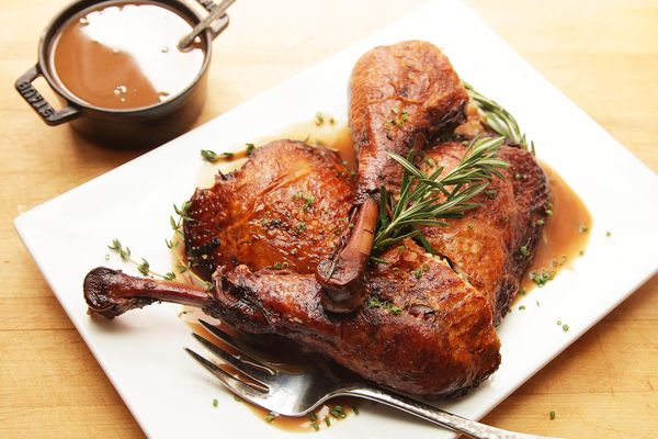 Overhead view of red wine-braised turkey legs on a white plate next to a pot of gravy.