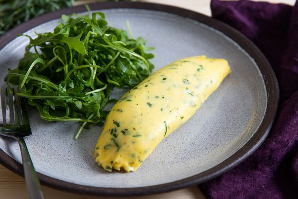 A classic French omelette on a place with arugula salad.