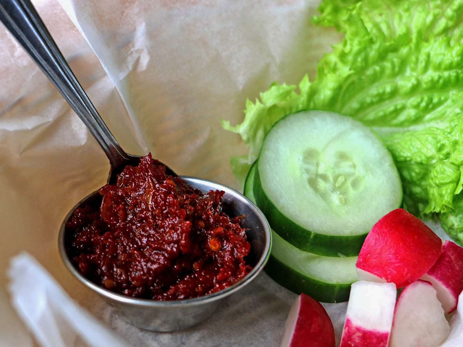 A small silver bowl of dark red hot pepper dip (jaew bong) with a spoon dipped into it, next to raw cucumber, radish, and lettuce