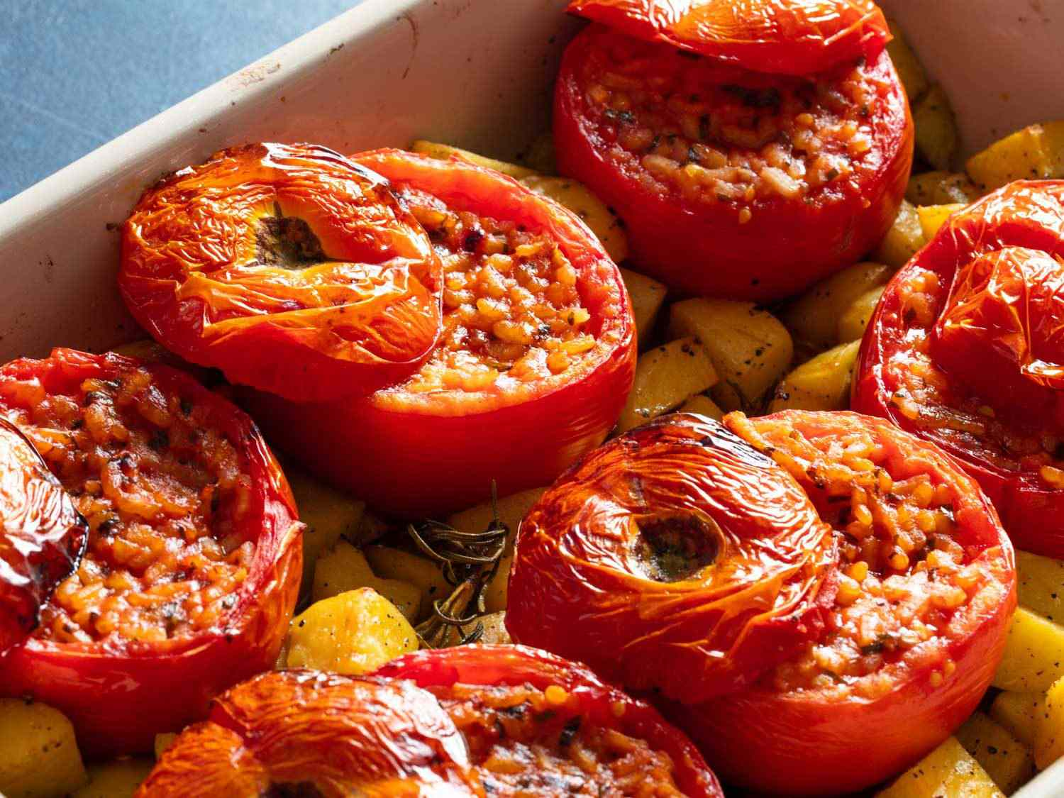 Close-up of rice-stuffed tomatoes in a baking dish with potatoes.