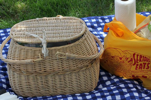A wicker picnic basket on a blue checkered tablecloth spread on the grass outdoors. There is a Serious Eats bag with paper towels and other picnic supplies next to the basket.