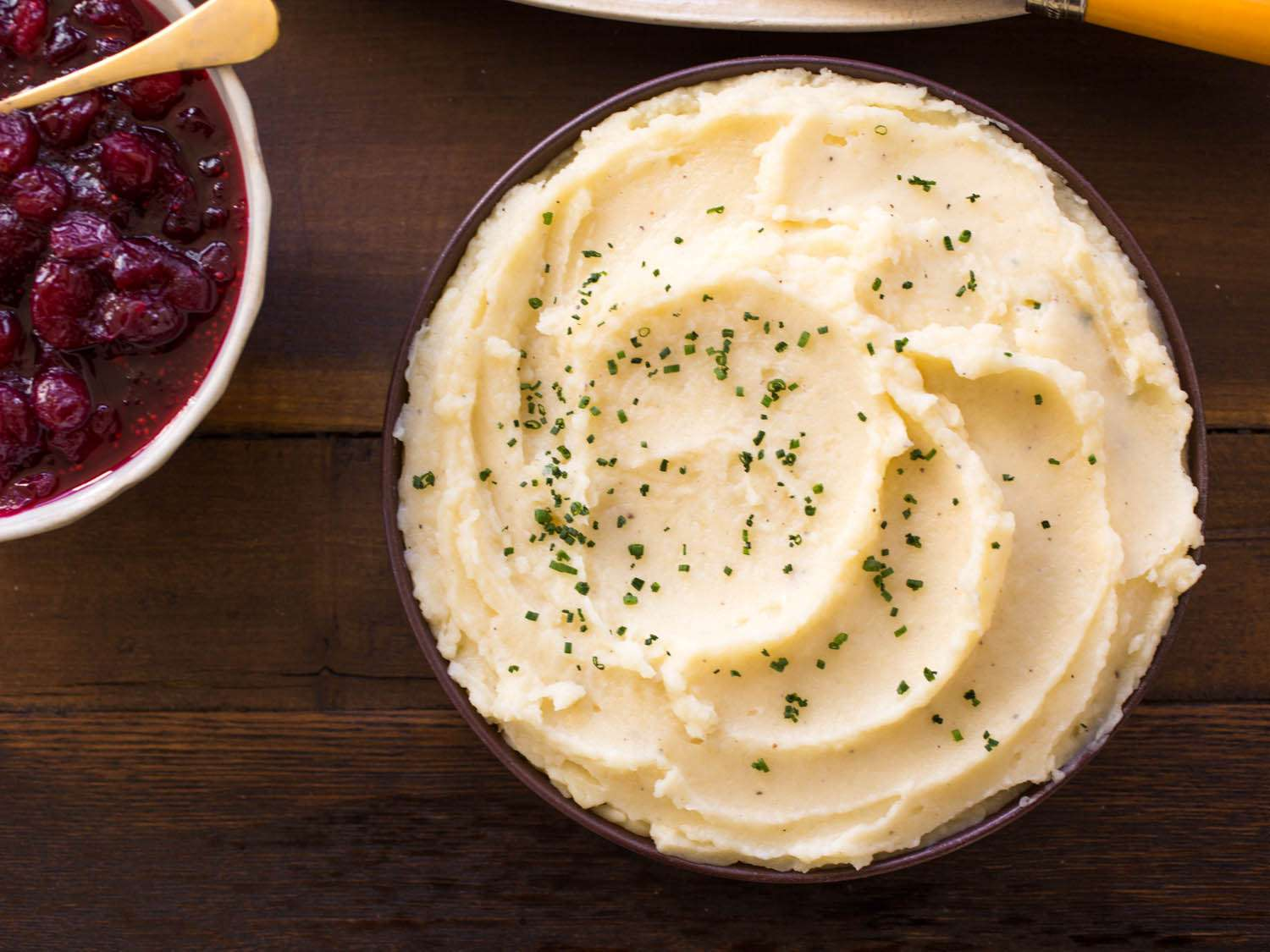 Overhead shot of a bowl of mashed potatoes and a dish of cranberry sauce