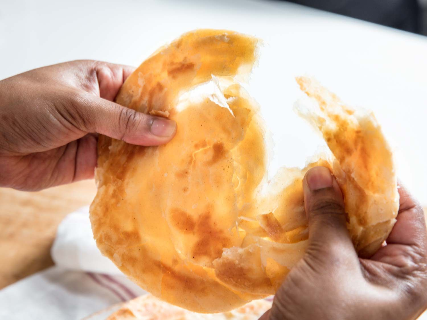 Paratha (Indian flatbread) being pulled apart by two hands.