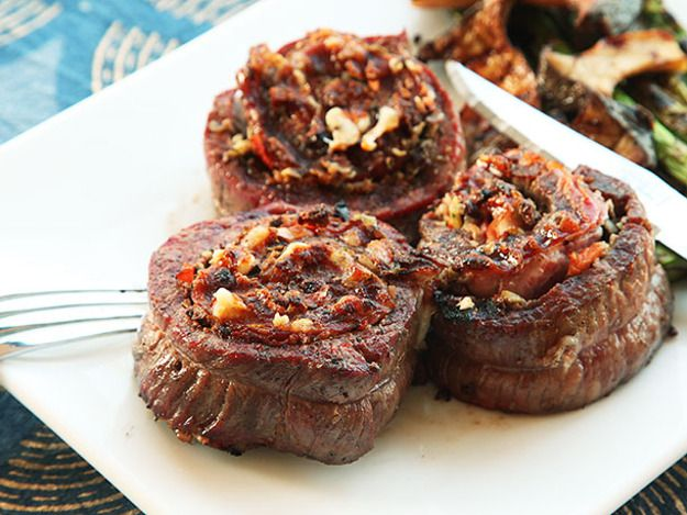 Grilled steak pinwheels stuffed with muffuletta sandwich–inspired fillings (olives, provolone cheese, and cold cuts)