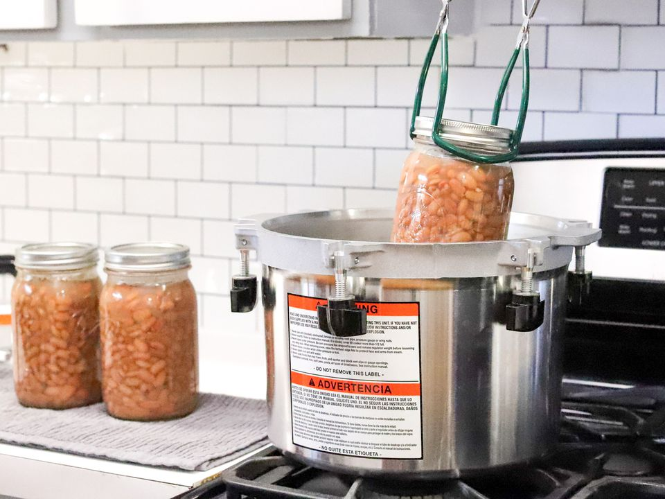 a jar of beans being lowered into an All-American brand pressure canner