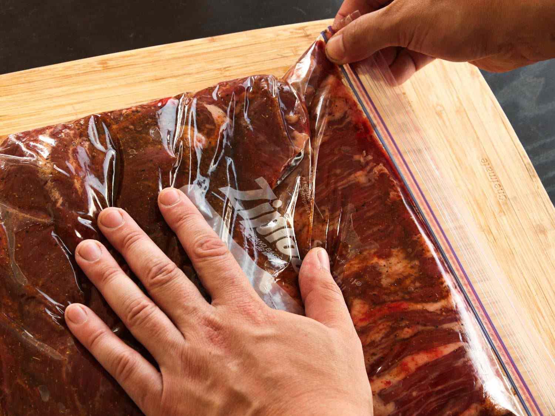 Hands sealing a plastic zipper-lock bag full of marinating skirt steak for fajitas.