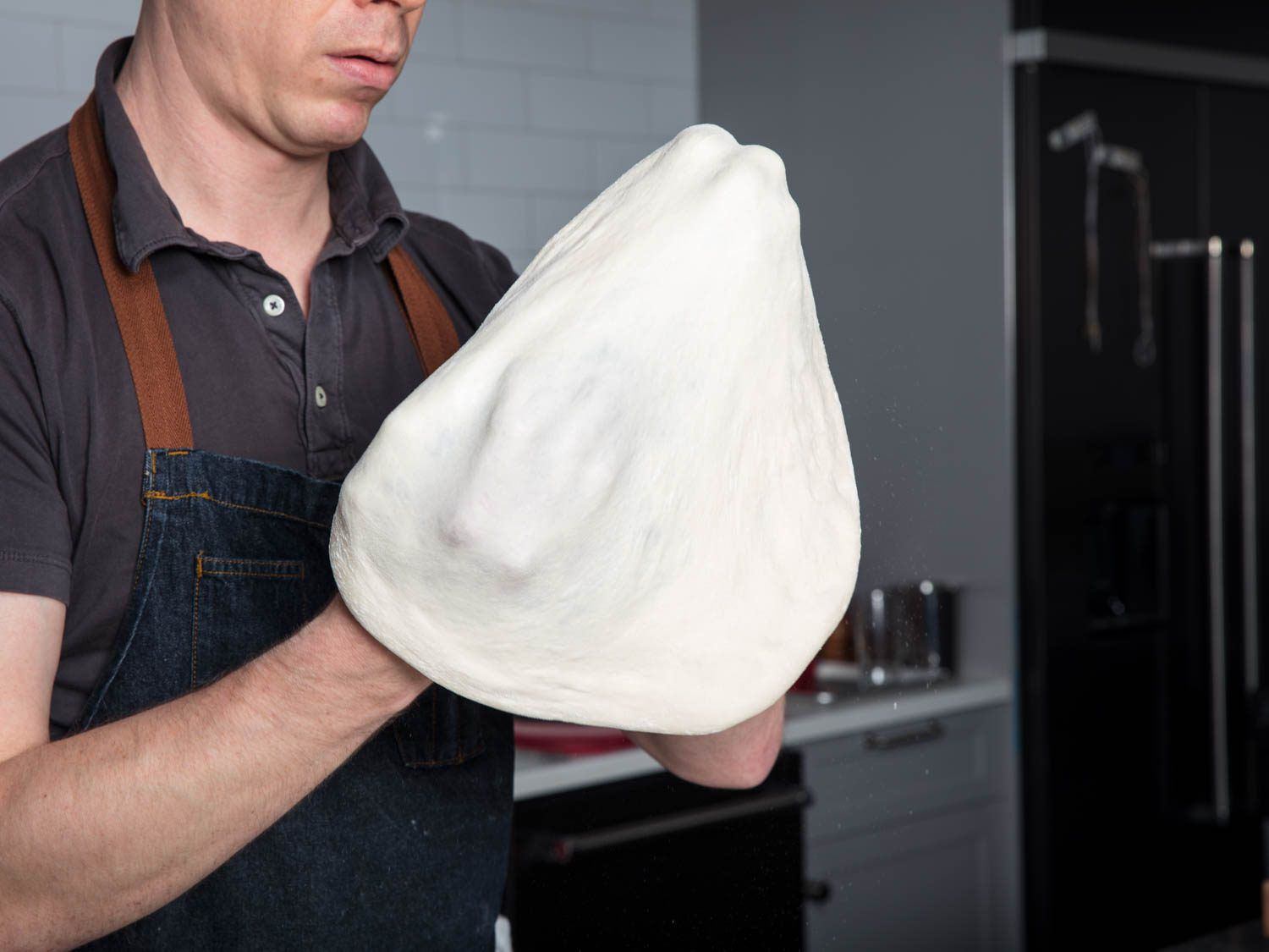 Stretching pizza dough by hand.