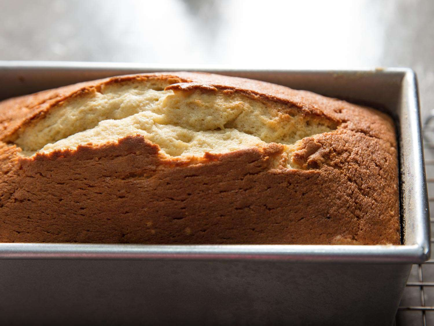 The cracked and split top of sour cream pound cake in a loaf pan