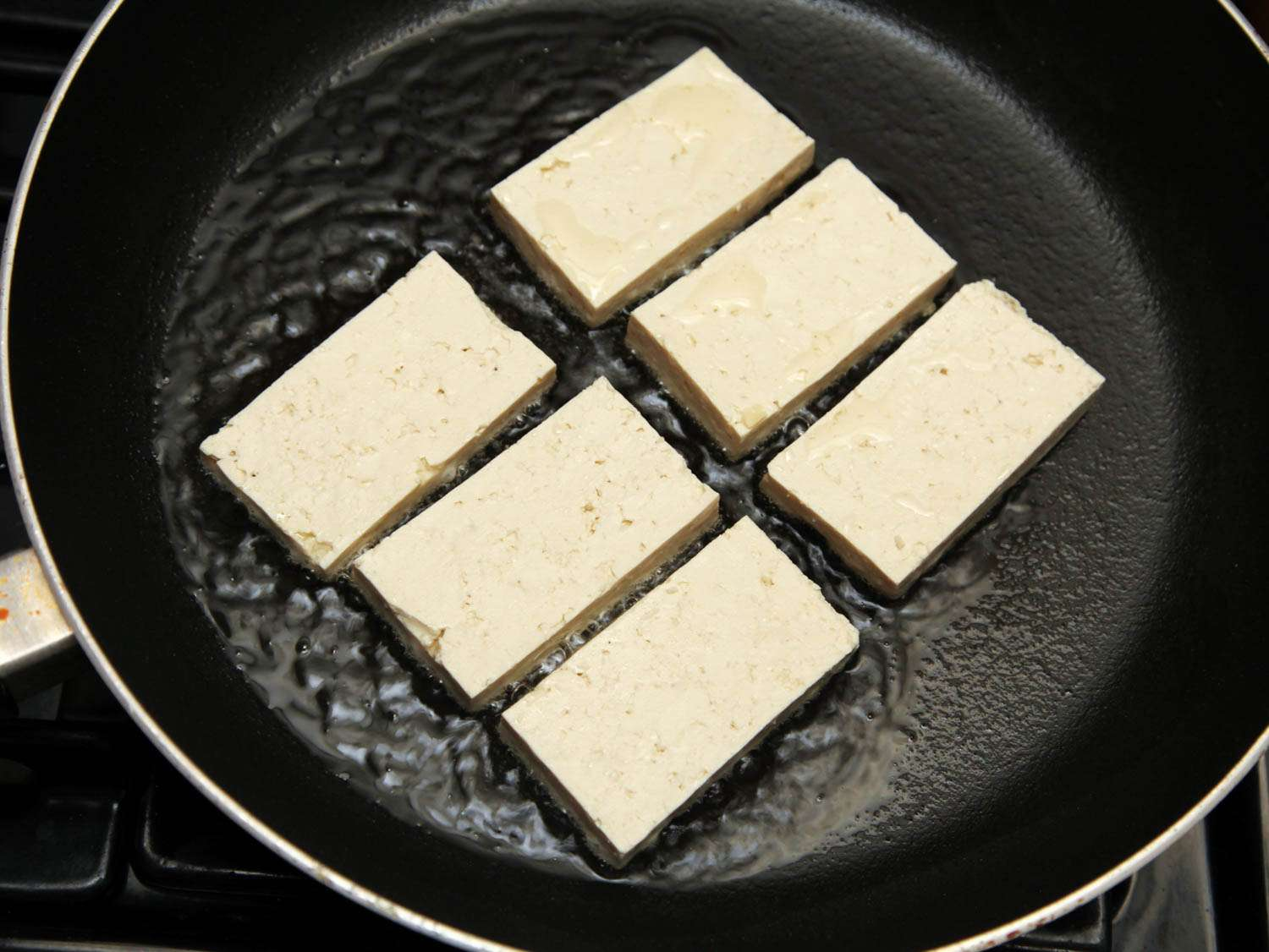 Tofu frying in a skillet.