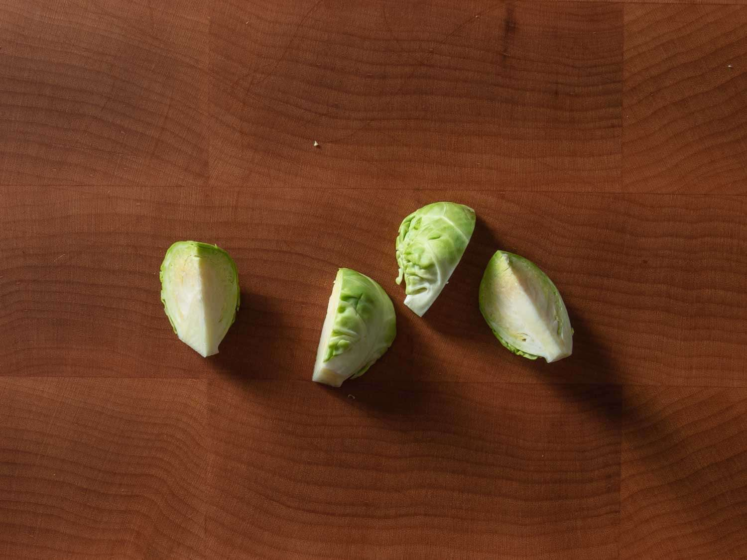 A Brussels sprout that has been cut into quarters lengthwise through the core.