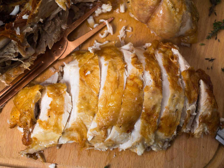 Slice, deep fried turkey breast on a cutting board.