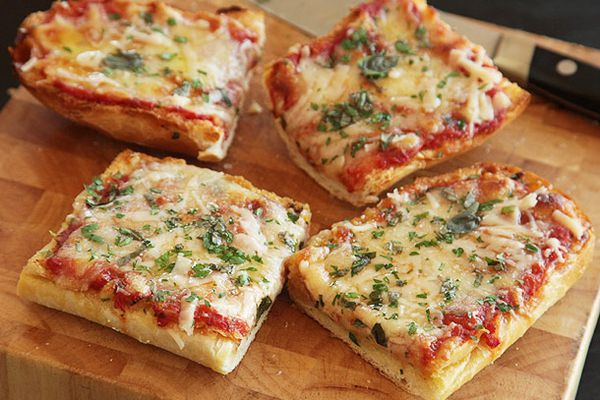 Four pieces of French bread cheese pizza on a wood cutting board.
