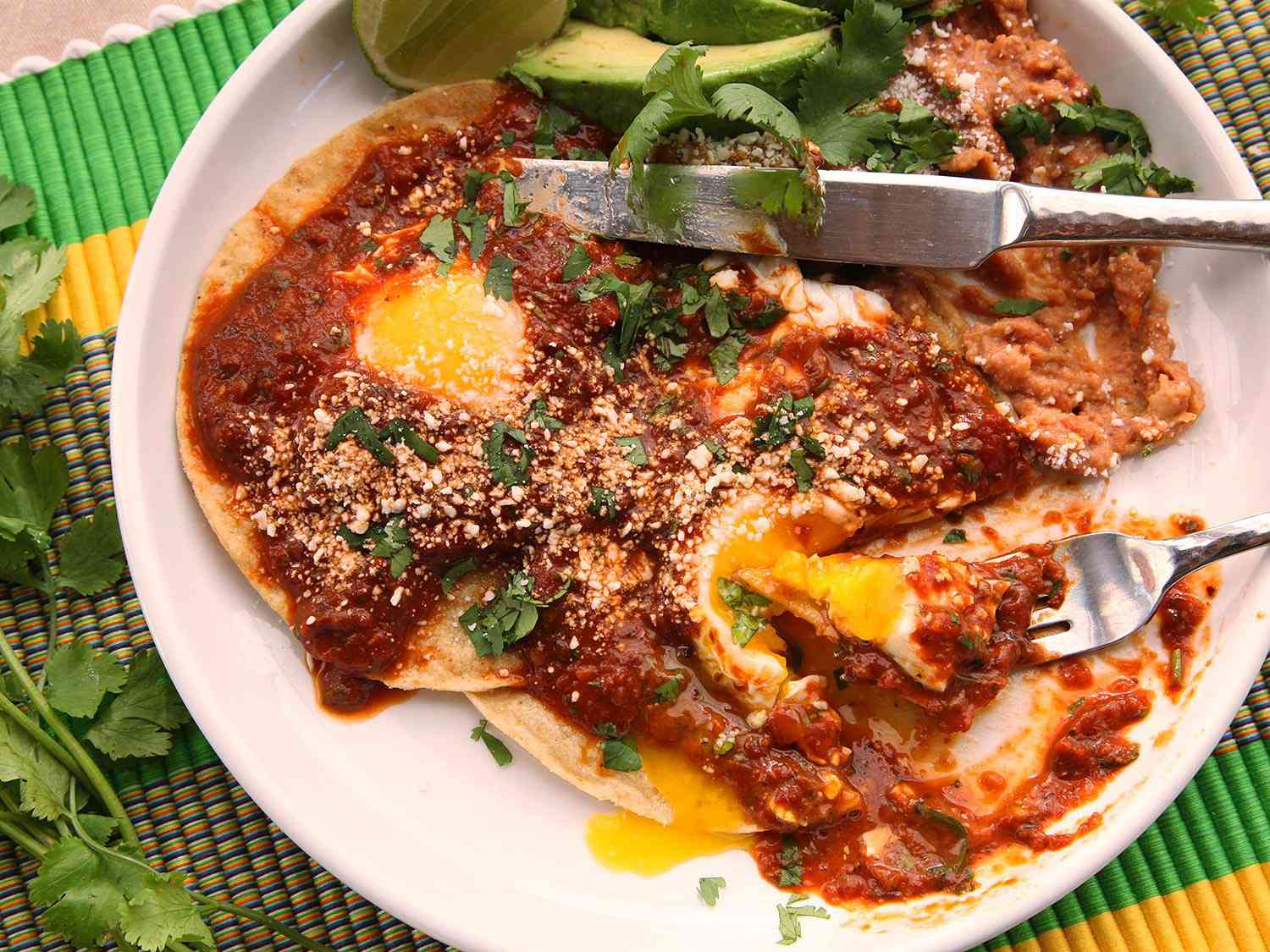 Quick and Easy Huevos Rancheros With Tomato-Chili Salsa on a plate with avocado slices, a lime wedge, and a fork and knife.