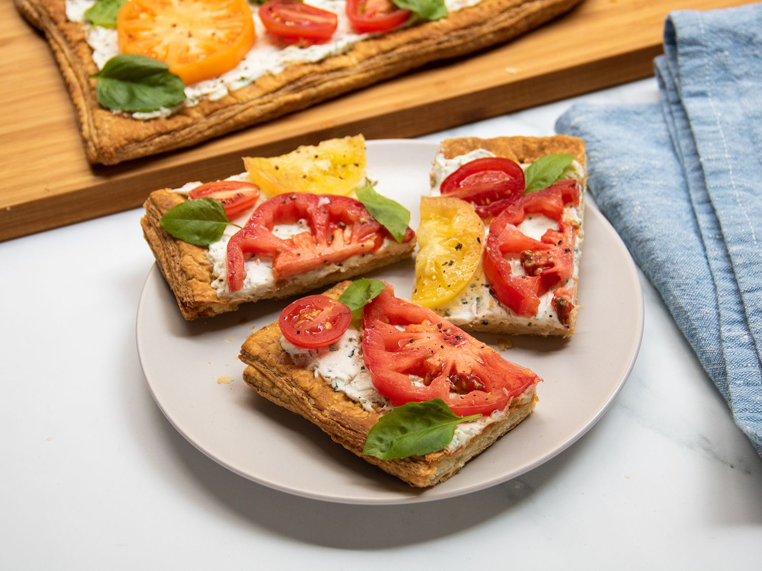 Slices of tomato tart on a plate, set in front of a cutting board with the rest of the tomato tart