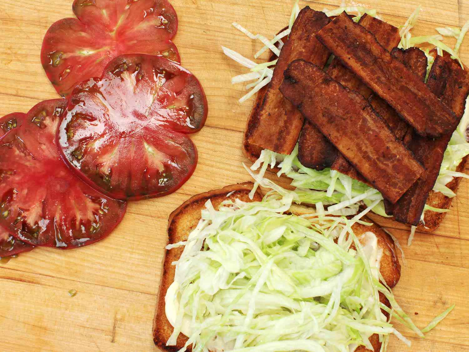 Assembling a BLT: sliced tomato next to a slice of toasted bread piled with mayo and shredded lettuce and another toast slice layered with bacon and lettuce